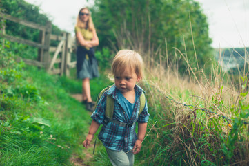 Little toddler walking in countryside with mother