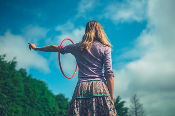 Young woman with hula hoop outdoors