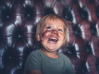 Laughing toddler with lipstick on face