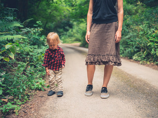 Mother and toddler walking in forest