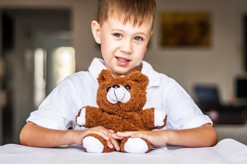 Funny and naughty Caucasian child with a toy teddy bear. Happy childhood concept.