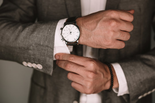 closeup fashion image of luxury watch on wrist of man.body detail of a business man.Man's hand in a grey shirt with cufflinks. Tonal correction