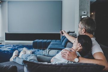 adult man with remote controller embracing girlfriend and watching tv on sofa at home