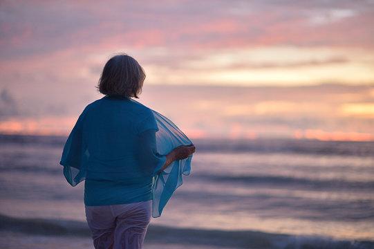 Portrait of happy elderly woman at sunset