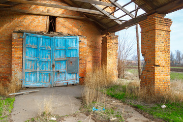 The entrance in the old abandoned brick shed with the blue gate