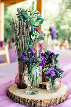 Purple lavender wedding. Table decor with dry lavender, green and white flowers. Candles, wooden rustic vases, Glass jars, lace bottles, sawed wood.