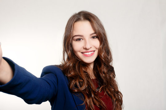 technologies, business, beauty and lifestyle concept - Portrait of young beauty woman doing selfie on grey background.