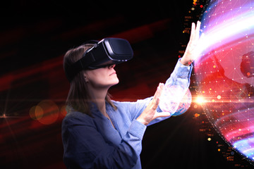 Woman with VR-glasses/A woman interacts with virtual reality. VR-technology and wearable tech concept. A woman wearing VR-glasses. Futuristic scene of  wearing virtual reality headset