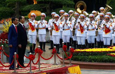 Indonesia's President Joko Widodo and Vietnam's President Tran Dai Quang attend the welcoming ceremony at the Presidential Palace in Hanoi,