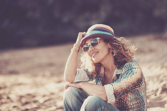 Happy beautiful cheerful caucasian woman middle age sitting at the beach and enjoying the summer time. smile and relax after work. vacation and travel concept with attractive and aged people