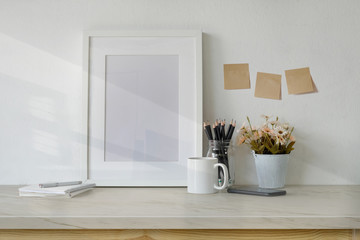 Mockup workspace table with white poster frame, coffee mug, notebook and supplies.