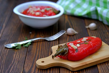 Appetizer, roasted pickled sweet red pepper on a wooden board. Serbian cuisine.