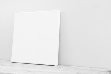 Mock-up poster frame in neutral gray interior.  White canvas, side view.