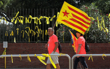 "A man carries an ""Estelada"" (Catalan separatist flag) as he walks past yellow ribbons during Catalonia's national day 'La Diada' in Barcelona"
