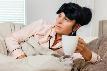 Woman with a cup of coffee in bed