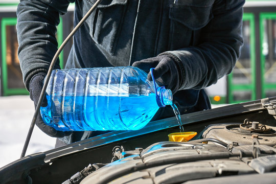 Filling a windshield washer tank of a car by antifreeze in winter outdoors