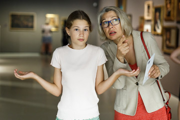 Tutor examining girl in museum