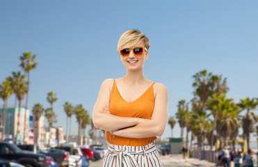 travel, tourism and summer holidays concept - happy smiling young woman in sunglasses over venice beach background in california