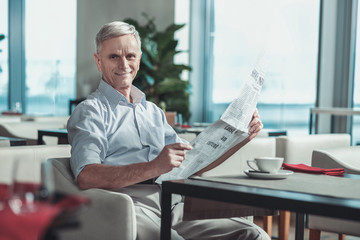 Have a look. Handsome male person holding newspaper in both hands while being in cafe