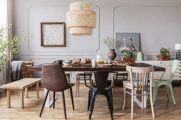 Chairs at wooden dining table under lamp in dining room interior with posters and flowers. Real photo
