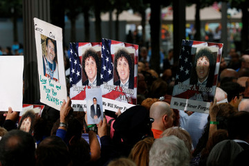 Guests hold signs with names and pictures of victims, during ceremonies marking the 17th anniversary of the September 11, 2001 attacks on the World Trade Center, at the National 9/11 Memorial and Museum in New York