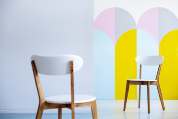 Two white chairs facing each other in a bright office interior with pastel decorations. Real photo with blurred foreground