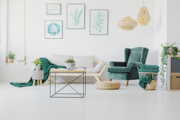Green accents, graphics and modern coffee table in a living room interior. Real photo