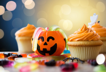 halloween and holidays concept - cupcakes or frosted muffins with party decorations and candies on wooden table over lights