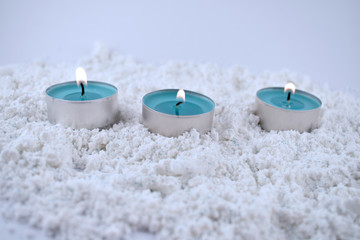 Blue tea candle stock images. Blue christmas candles on a snowy background. Christmas decoration background