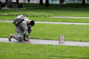 U.S. Army Reserve Sgt. Edwin morales honors his cousin Ruben Correa during ceremonies marking the 17th anniversary of the September 11, 2001 attacks on the World Trade Center, at the National 9/11 Memorial and Museum in New York