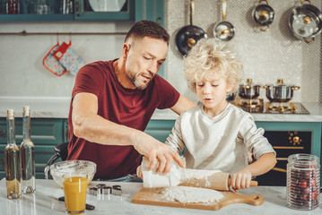 Some flour. Dark-haired father adding some flour to dough for future pie while son rolling out pastry