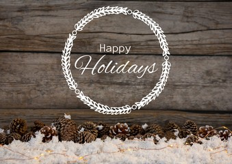 Happy holidays text with wood and pine cones in snow