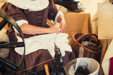 Cropped image of weaver in Middle Agesl clothes make yarn on spinning wheel. Medieval crafts, occupation. The concept of historical development of weaving in England. Selective focus. Copy space.