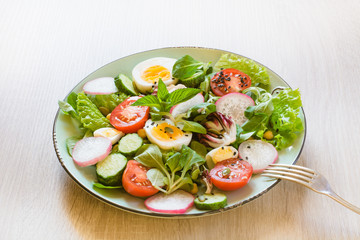 Healthy salad with vegetables and eggs on wooden table. Close up, copy space. Balanced diet for weight loss.