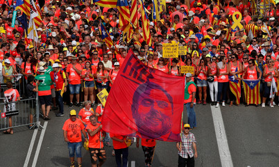 People hold a banner depicting dismissed Catalan Vice President Junqueras as they gather for a rally on Catalonia's national day 'La Diada' in Barcelona
