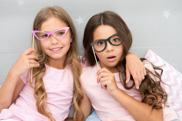 Something went wrong way. Children posing with confused face photo booth props. Pajamas party in bedroom. Friends cute and cheerful posing eyeglasses accessories. Girls having fun pajamas party