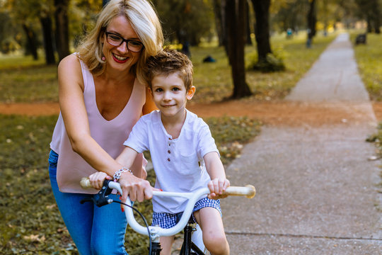 Little boy learning to drive a bike with his mom