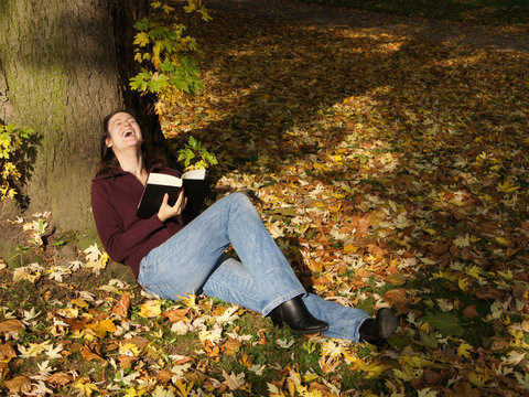 woman laughing out loud while reading a book in autumn scene