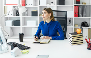 A young girl sits at a computer desk and holds a yellow marker in her hand. Before the girl lies an open book.