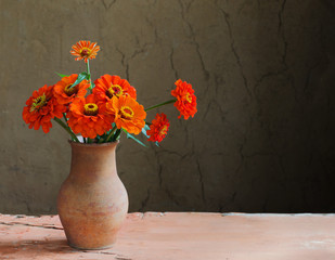 flowers in jug on old wooden table