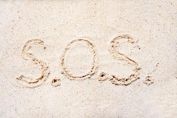"Handwriting words ""S.O.S"" on sand"