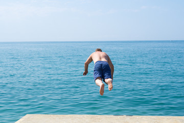 A man jumps into the sea from the pier