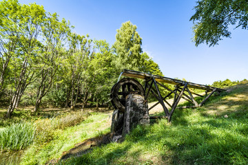 Old water mill on a meadow with green grass