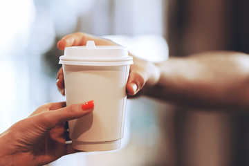 Barista passes coffee to a visitor in a popular coffee shop, hands and a glass of coffee are shot close-up.