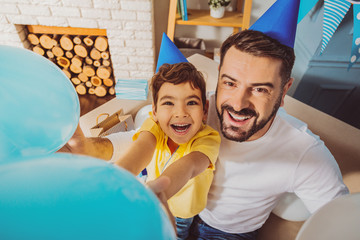 Best party. Happy positive boy and man fooling with balloons while laughing