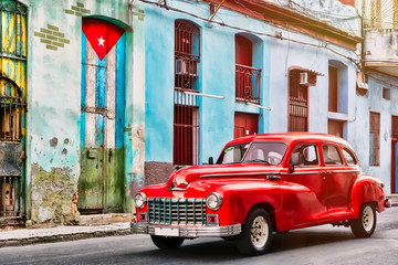 Fototapeten Bekannte Orte in Amerika Classic car and and old building with the cuban flag in Old Havana