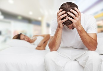 Upset man sitting and woman laying on bed