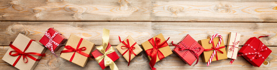 Christmas gift boxes on wooden background, banner, copy space, top view