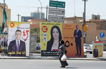 A Kurdish woman walks past campaign posters ahead of regional elections, in Erbil