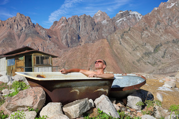Middle-aged man taking a bath outdoors